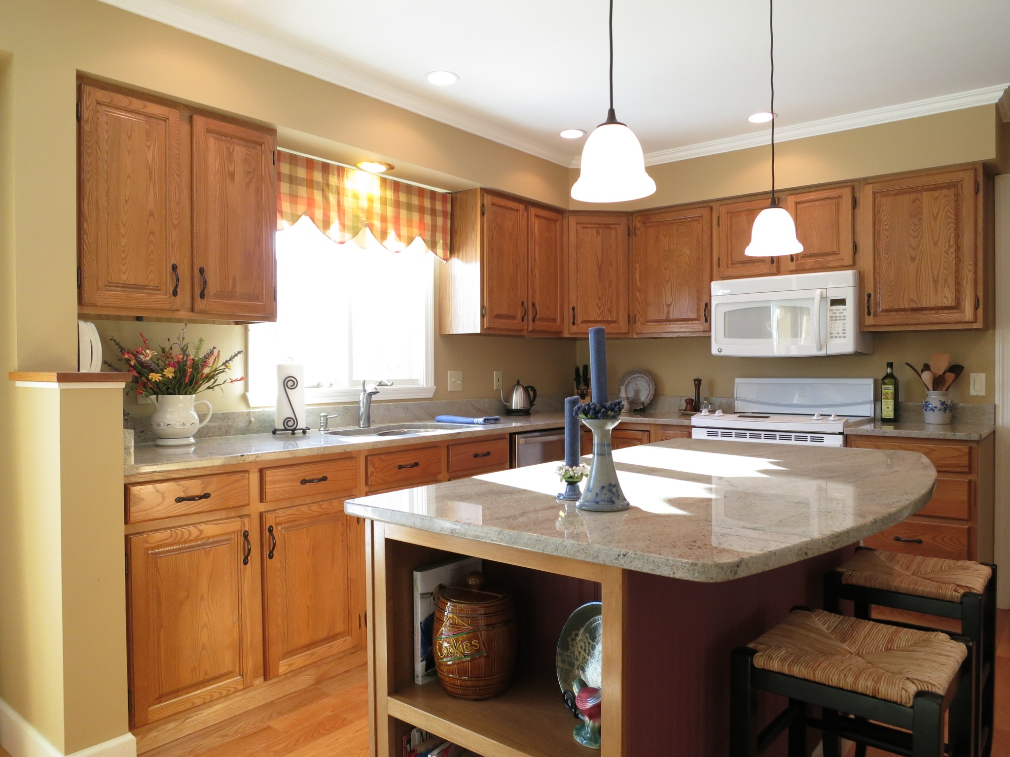 The kitchen features granite countertops, a central island with seating, pantry and newer appliances.